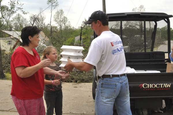 Durant Casino Resort employee Shawn Lyday, right, delivers hot meals to two Tushka residents affected by the April 14 tornado. (Photo by BRET MOSS, Choctaw Nation of Oklahoma)
