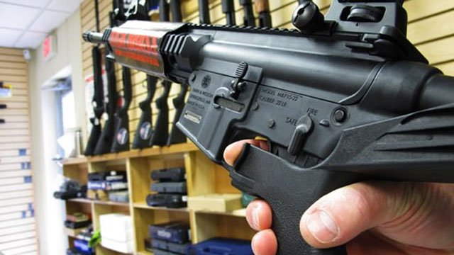 "A gun store  employee demonstrates how a ""bump"" stock works. (AP Photo/Allen Breed)"