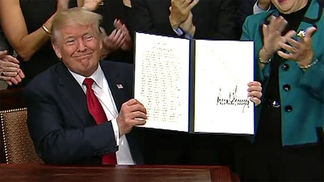 President Donald Trump displays his executive order on health care. (CNN)