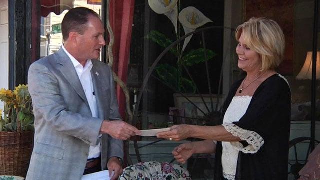 Sherman Mayor David Plyler presents a check to downtown merchant Leslie Archer. (KTEN)