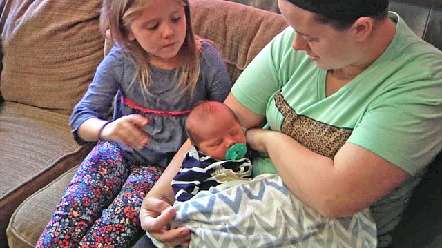Lacy Hamer tends to Rowdee as another child looks on. (KTEN)