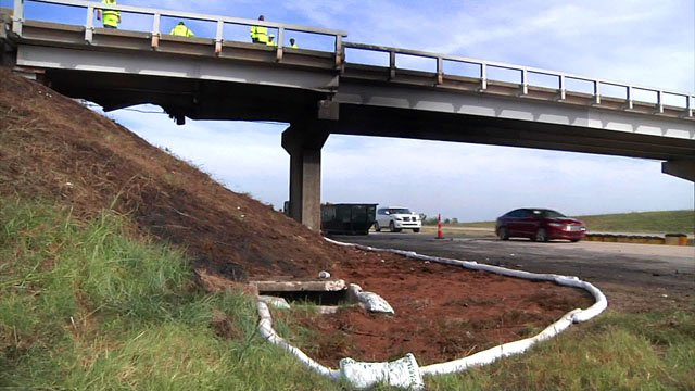 Workers examine the damage to the Jacobs Road bridge after it was hit by an 18-wheeler on Wednesday. (KTEN)