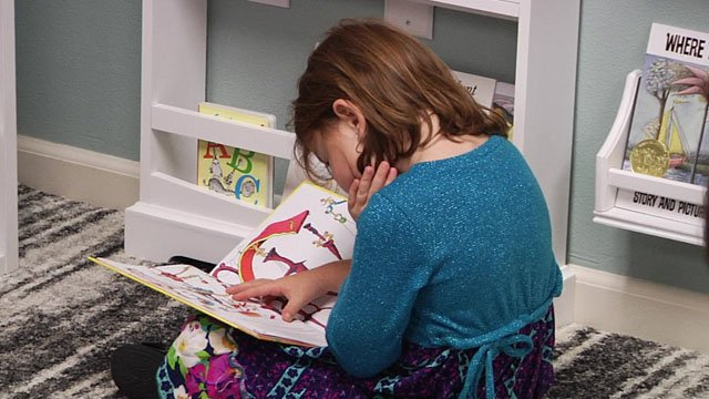 A girl enjoys a book at the new Rachael Trumbull Memorial Library at the Grayson County Children's Advocacy Center. (KTEN)