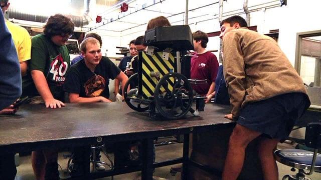 The Denison High School Robotics Team examines its latest creation. (KTEN)