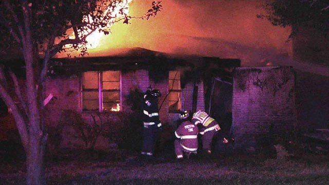 Firefighters at the scene of a house fire in Denison. (KTEN)