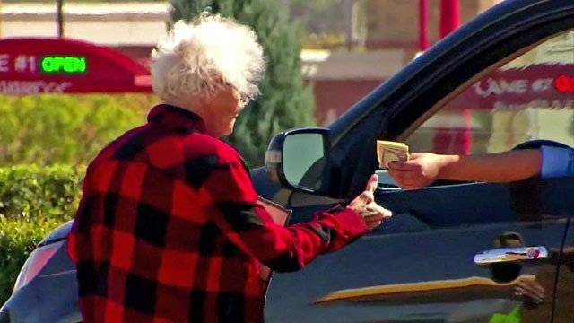 A woman accepts money from a motorist at a Sherman intersection. (File/KTEN)