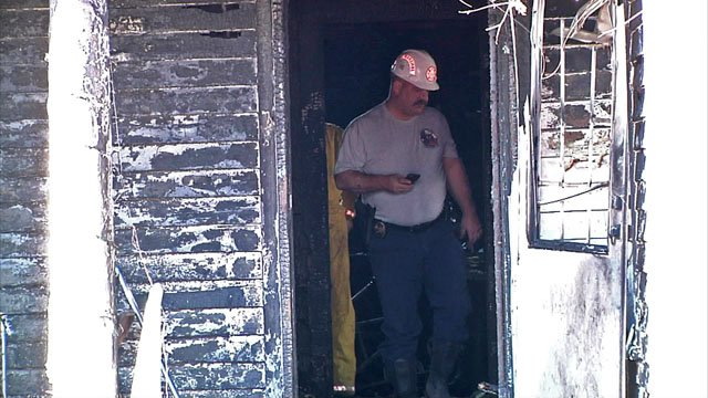 A fire investigator surveys the damage at the Gainesville residence where two children died. (KTEN)