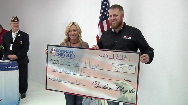 Colt Floyd accepts a check after being named the recipient of the November Texoma Hero award. (KTEN)