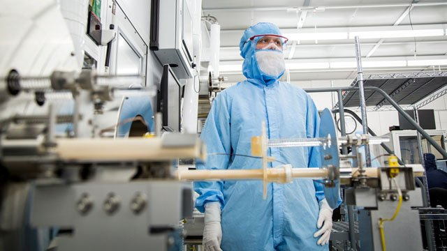 A Finisar worker wears specialized gear in the manufacturing area of the company's Allen Texas facility