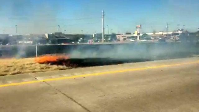 A grass fire burned in the U.S. 75 median across from Sherman Town Center on Wednesday. (KTEN)