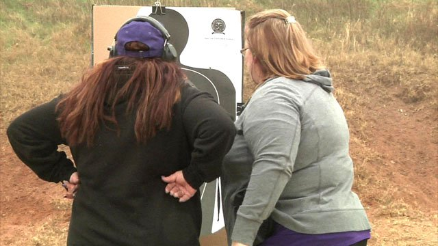 Members of The Well Armed Woman examine a target. (KTEN)