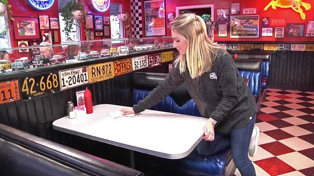 An MG's Restaurant employee uses a bleach solution to clean tables. (KTEN)