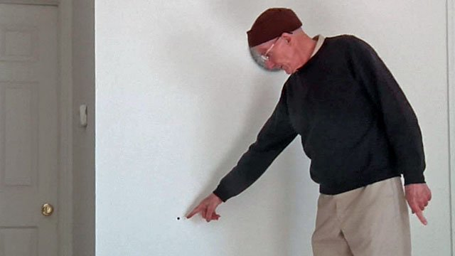 Dennis Reif points to a bullet hole in the wall of his home near Ada. (KTEN)