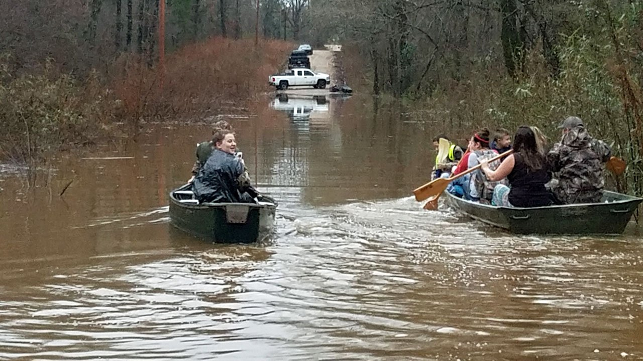 Families near Rufe, Oklahoma, use boats to bypass the flooded road to their homes. (Photo courtesy Lisa Little)