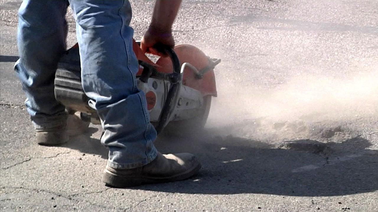 Workers repair potholes in Durant. (KTEN)