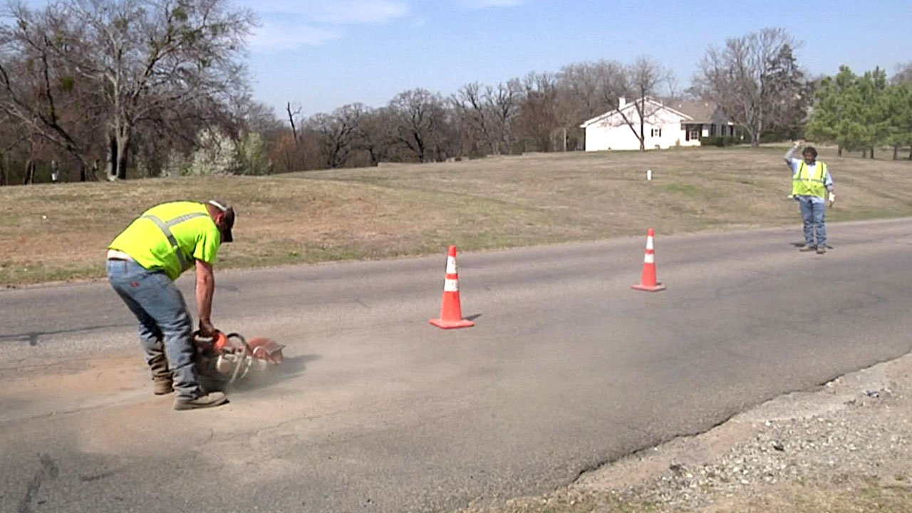 Workers repair potholes in Durant. (KTEN)
