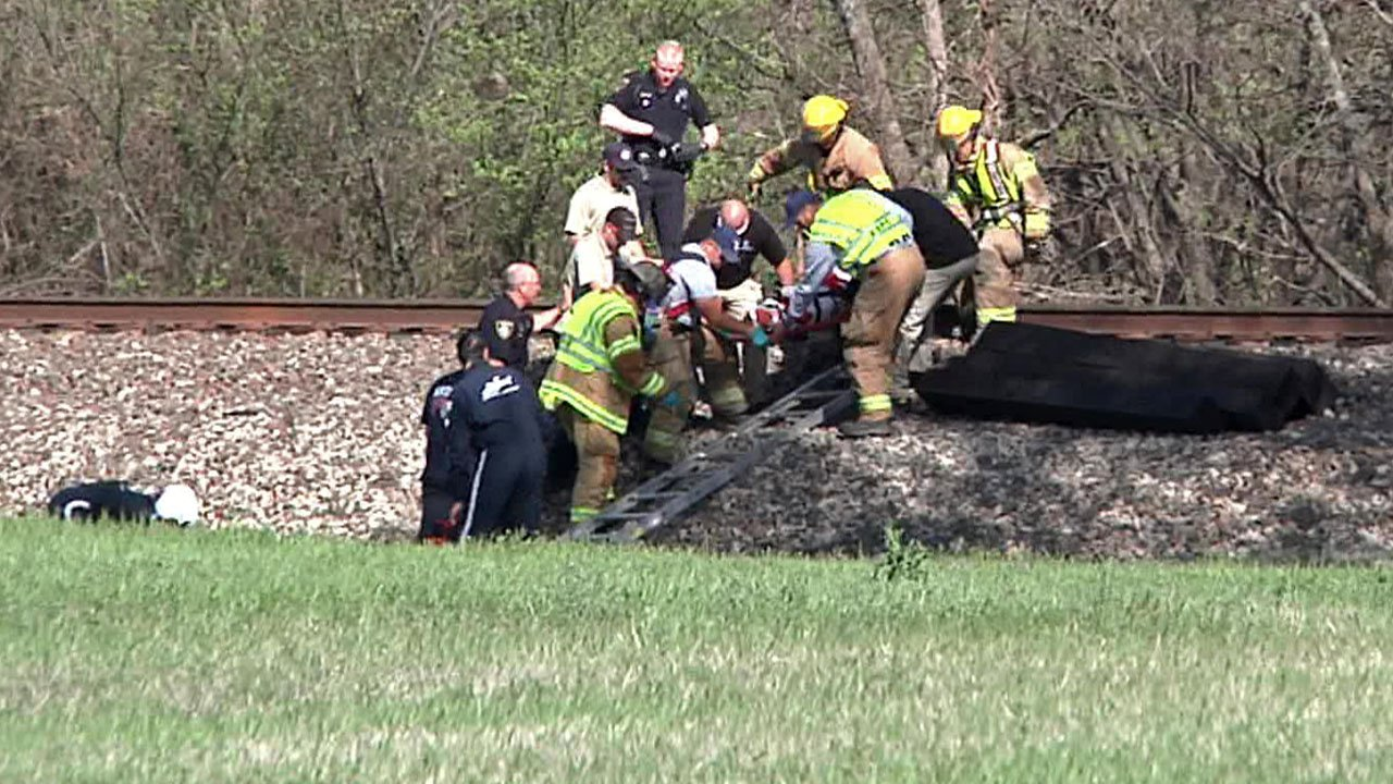 Emergency personnel take a woman to a waiting rescue helicopter after she was hit by a train in Ardmore. (KTEN)