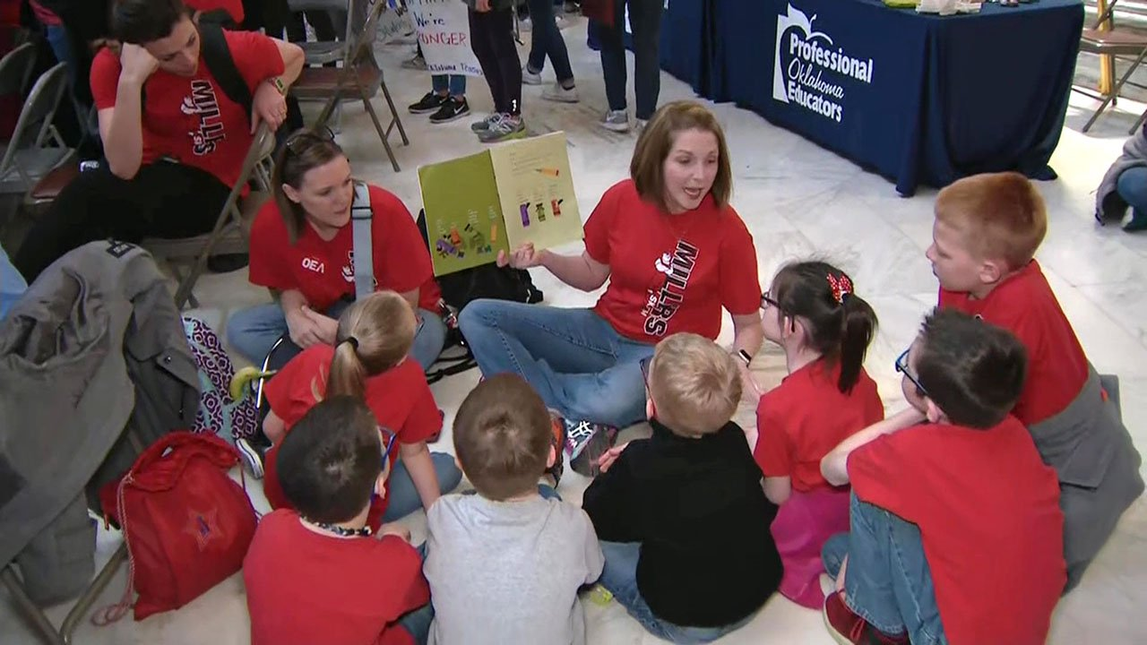 A teacher reads to students in a circle on the floor of the State Capitol. (CNN)