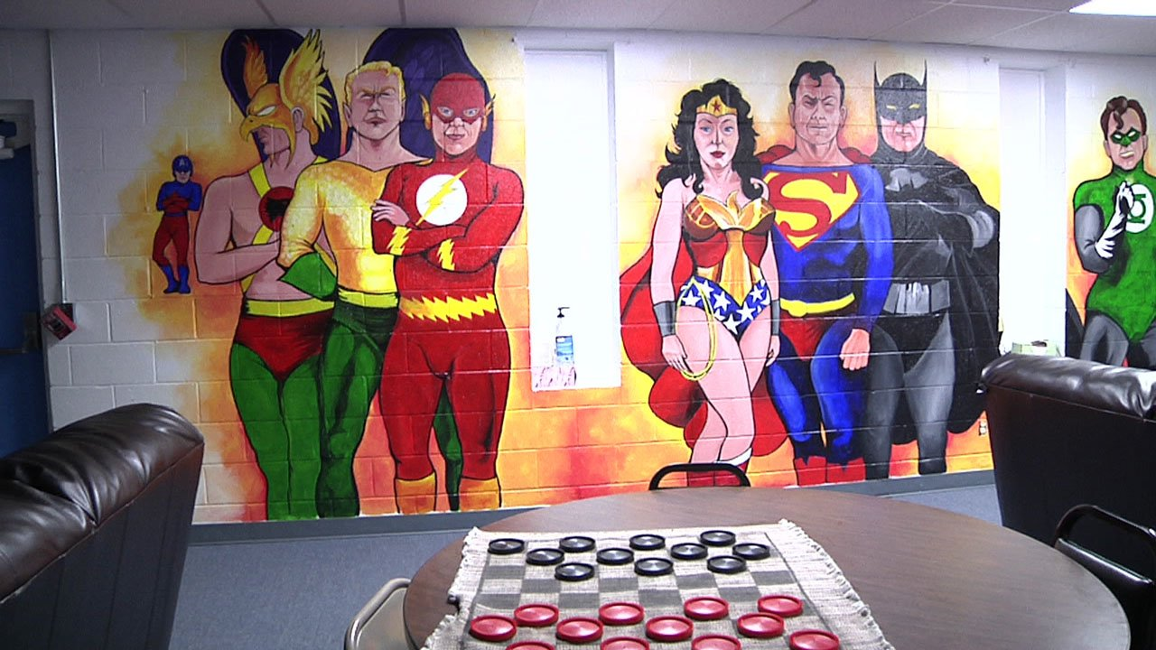 In another mural at the Durant Boys & Girls Club, artist Robert Rawls depicted superheroes. (KTEN)