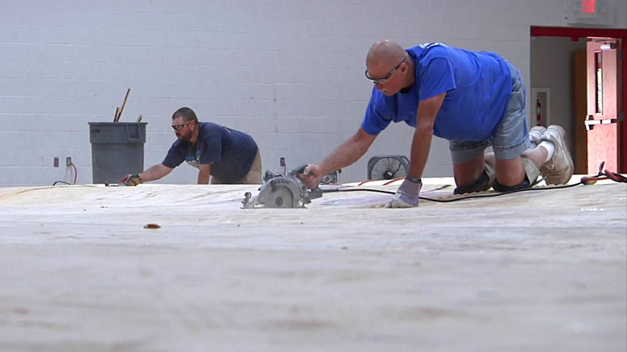 Workers were busy removing warped hardwood from the Ardmore Middle School gymnasium. (KTEN)