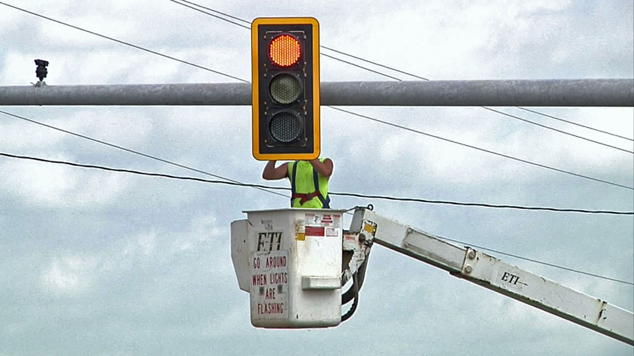 A worker aims the new signal light at U.S. 70 and Silo Road near Durant. (KTEN)