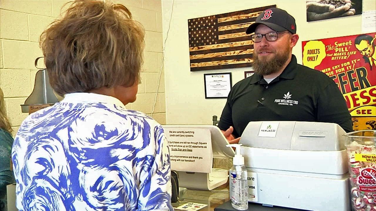 Todd Larkin talks with a customer at Pure Wellness CBD in Ardmore. (KTEN)