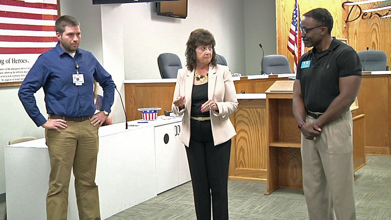 Denton City Council candidates Brian Hander, left, and Rayce Guess, right, wait for the coin toss by Mayor Janet Gott. (KTEN)