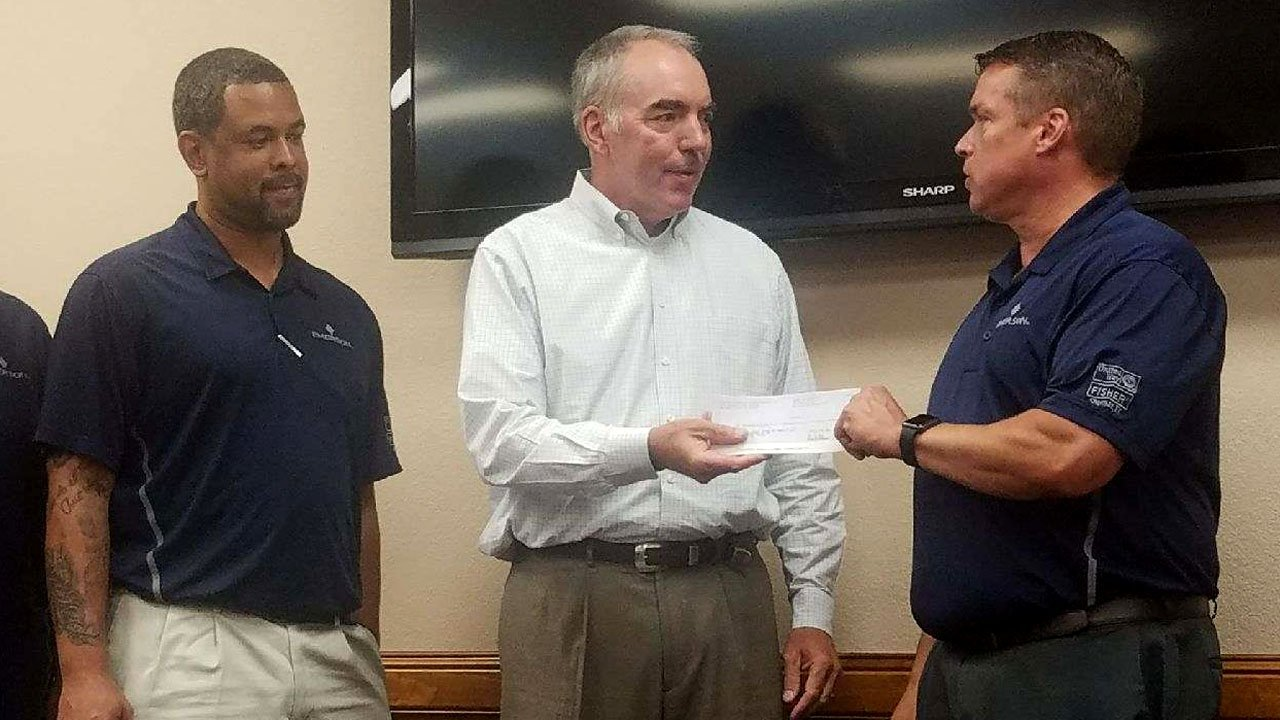 Emerson plant manager Mark Anderson presents a $1,000 check to the Boys and Girls Club of Sherman on June 19, 2018. (KTEN)