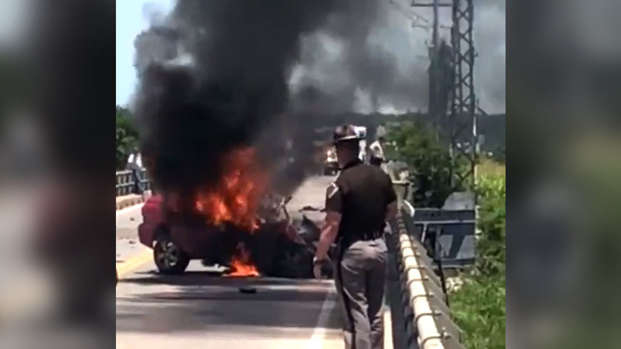 A trooper looks on helplessly as a car burns on the Roosevelt Bridge on June 21, 2018. (Courtesy Roy Wulf)