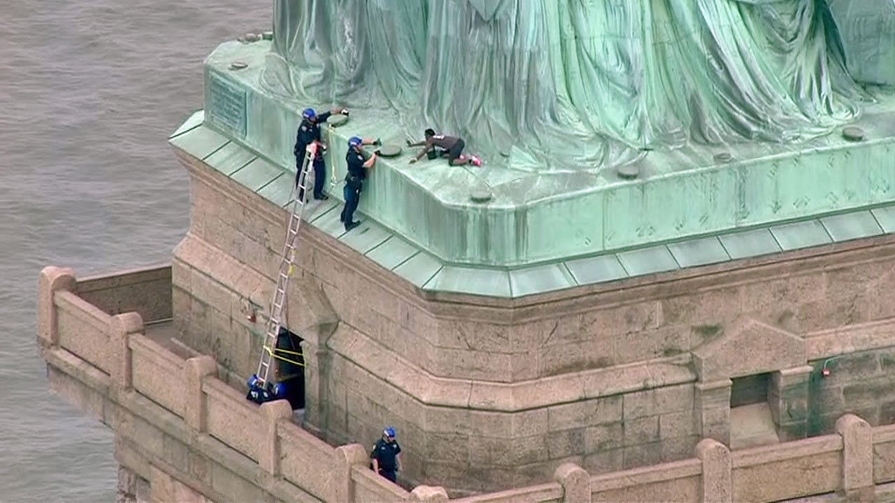 Police try to coax a climber down from the base of the Statue of Liberty. (WPIX via CNN)