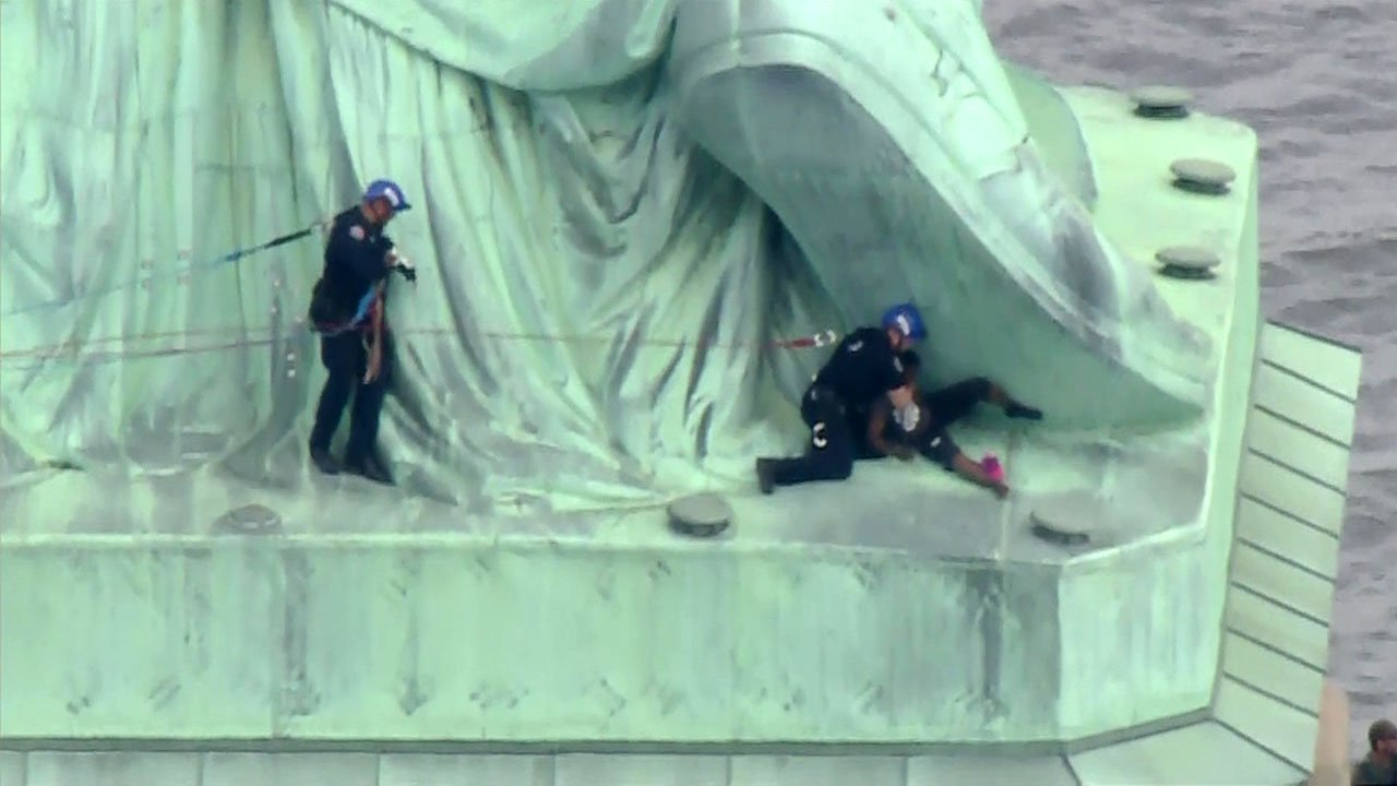 A New York police rescue team takes a woman into custody at the base of the Statue of Liberty. (WCBS via CNN)