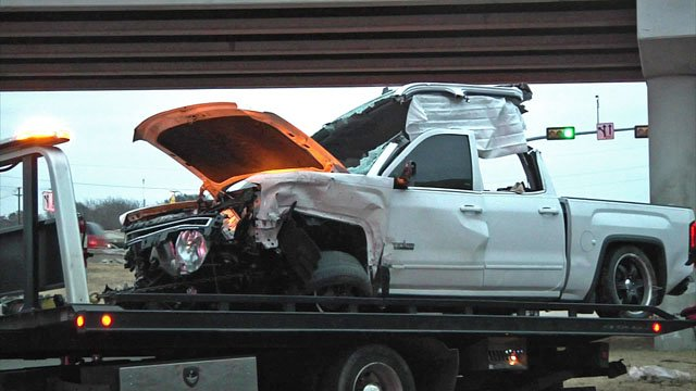 A pickup truck is moved from the U.S. 82 service road after plunging from the U.S. 75 overpass in Sherman. (KTEN)