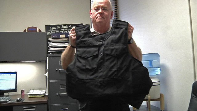 Denison police Lt. Mike Eppler holds a Threat Level III protective vest. (KTEN)