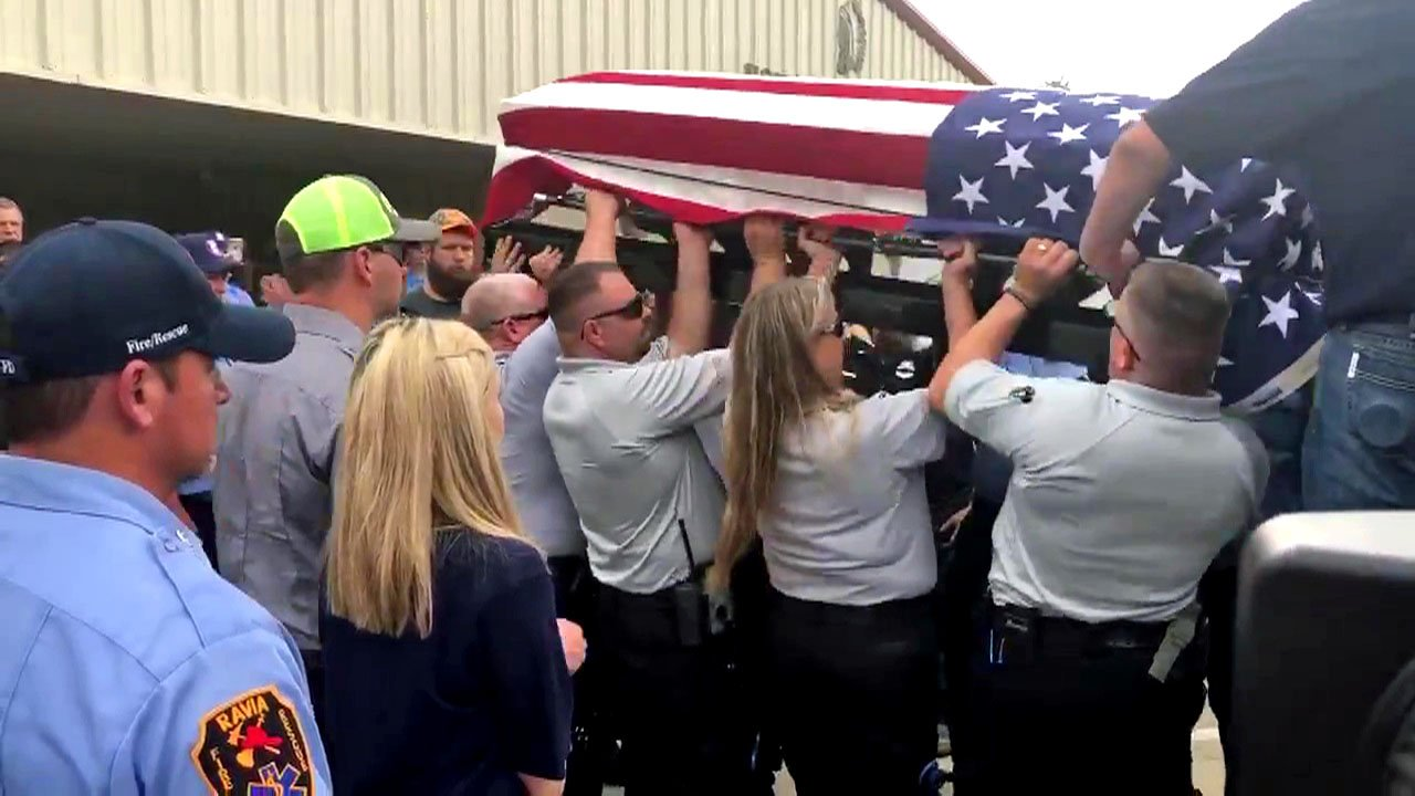 Pallbearers list the casket of Wapanucka Fire Chief Gary Reeder into a fire truck following a memorial service at the high school. (KTEN)