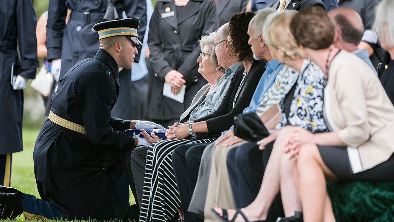 U.S. Army Capt. Lukas Findley presents the U.S. flag to Nancy Farrell, the sister of Staff Sgt. Robert Shoemaker. (U.S. Army photo by Elizabeth Fraser / Arlington National Cemetery)