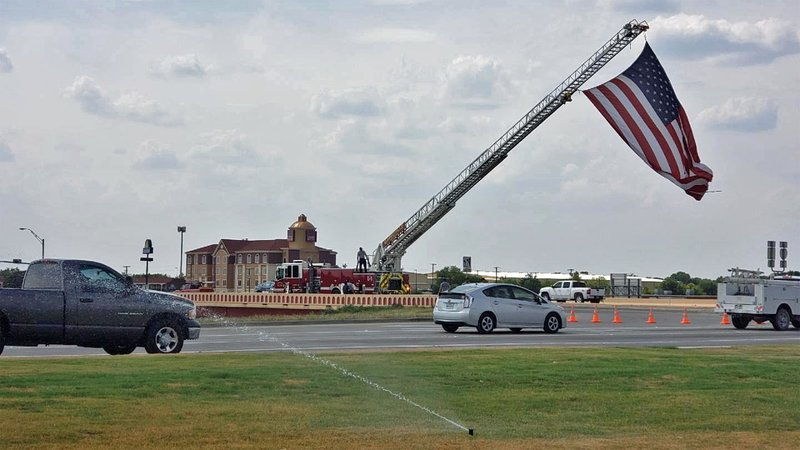 A large U.S. flag honored the funeral cortege of Dallas police Senior Cpl. Jamie Givens. (KTEN)