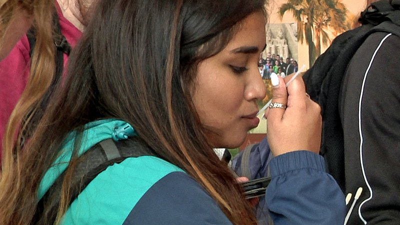 An Austin College student swabs her mouth for a sample to be added to a bone marrow registry. (KTEN)