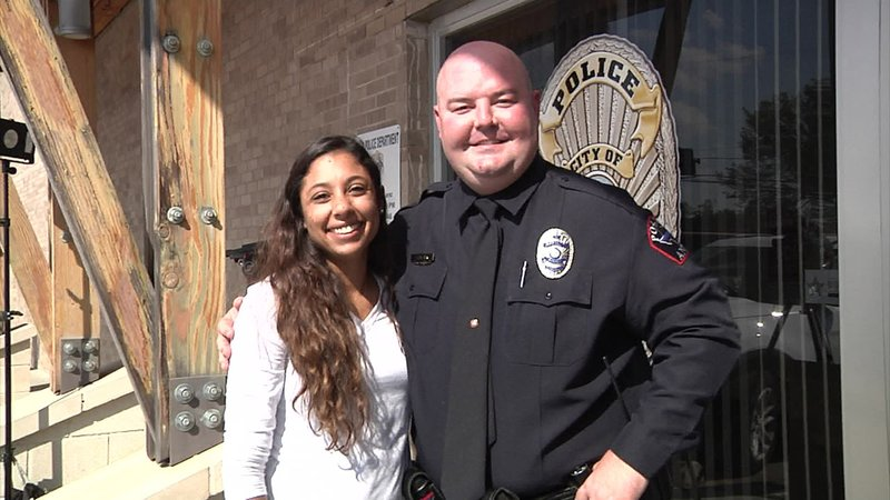 Megan Herriera poses with Anna police Officer Brandon Blair, who pulled her out of the way of an oncoming pickup truck. (KTEN)