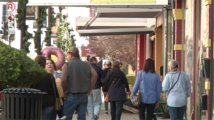 Patrons walk down the street with purchases from local businesses (KTEN)