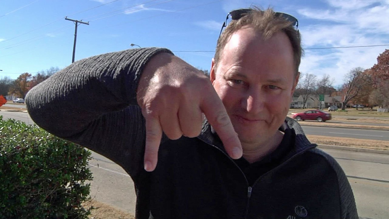 """Oklahoma players will risk a big penalty if they flash the """"horns down"""" sign that fan Barry Bowker displays. (KTEN)"""