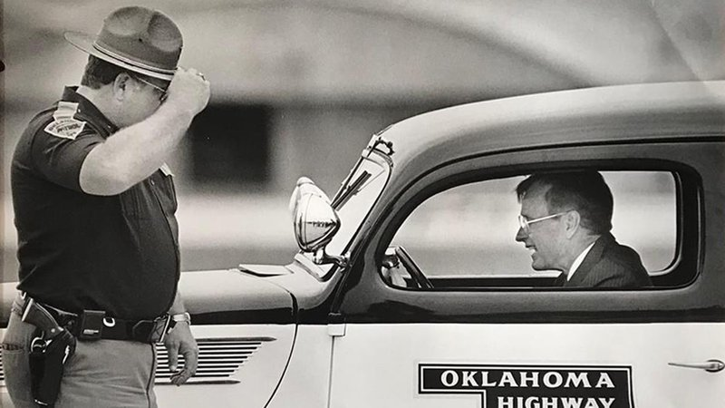 In this 1989 photo, Oklahoma Highway Patrol First Lt. Ken Perry is seen saluting George H.W. Bush in Tulsa. (OHP/Facebook)