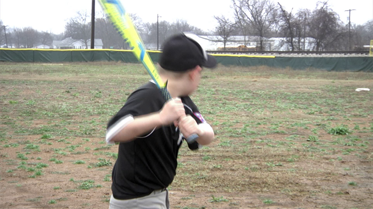 A youth baseball player stands ready to swing a bat at Ferguson Park