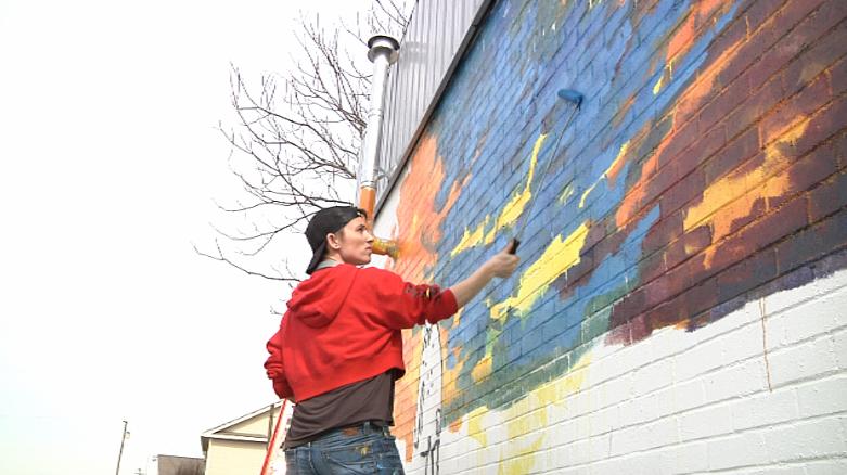 Mural artist Calina Johnson painting new mural in Van Alstyne