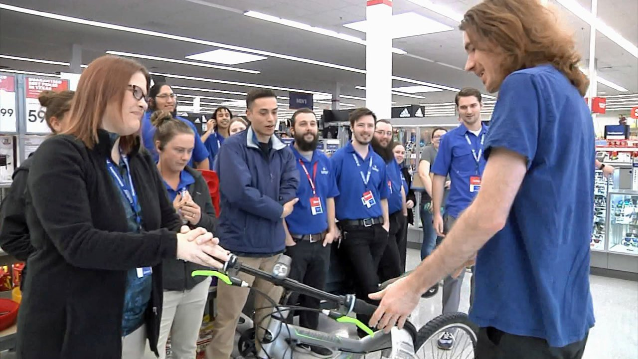 Academy co-workers present Jake Coulson with a new bicycle. (KTEN)
