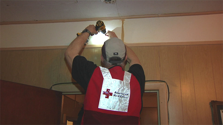 A Red Cross volunteer installs a smoke detector