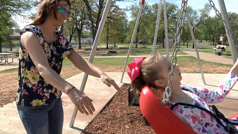 Morgan Anthony pushes her daughter Hadley on a special needs swing at Durant's Rocket Park. (KTEN)
