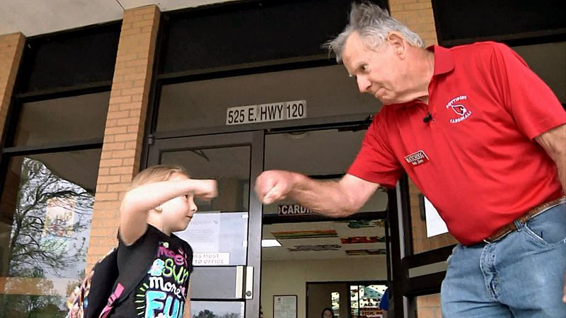 """Some youngsters get a fist bump from """"Mr. Jim"""" when they get to school in Pottsboro. (KTEN)"""
