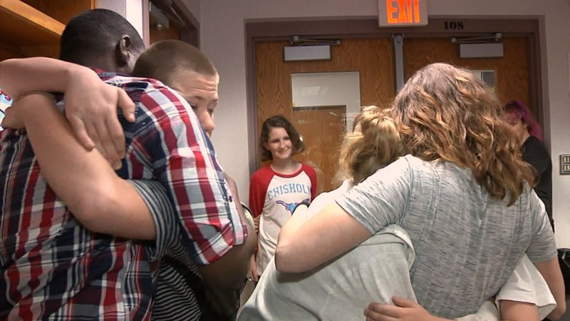 Tonya Rivera and her children give hugs to people who helped them recover from a fire. (KTEN)