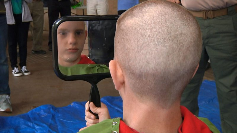 Cancer survivor Michael Gary gets a look at his new haircut. (KTEN)