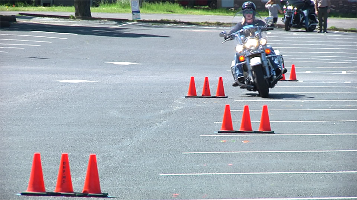 Motorcyclists weave through cones in a safety course taught by Oklahoma Highway Patrol troopers